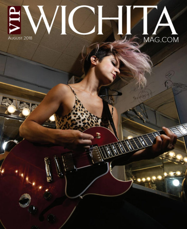 Jenny Wood playing guitar and rocking out on the cover of VIP Wichita